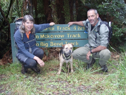 "Susan Ellis, kiwi dog ""Crete"" and dog handler, Scott Theobold pose for a photo at the start of the Whakanui Track"