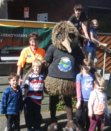 Rimu the Kiwi surrounded by children at the Planting Day for families at the Catchpool during Conservation Week 2013